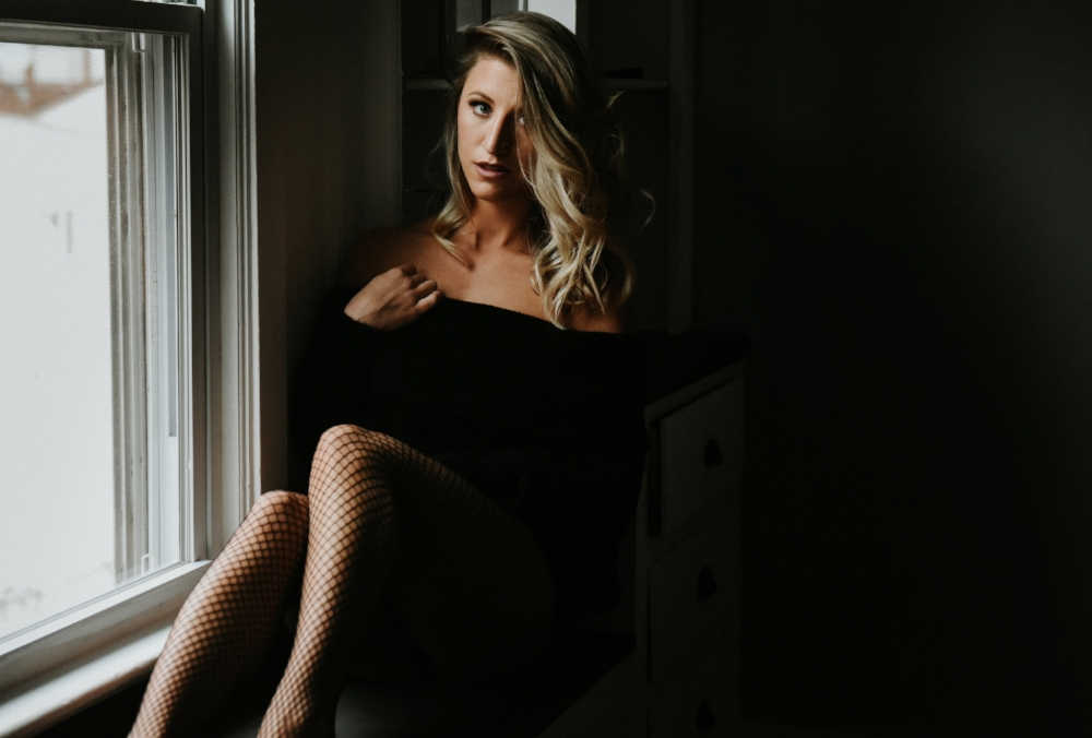 Blonde woman in black sweater fishnets sitting in window boudoir photography new york studio