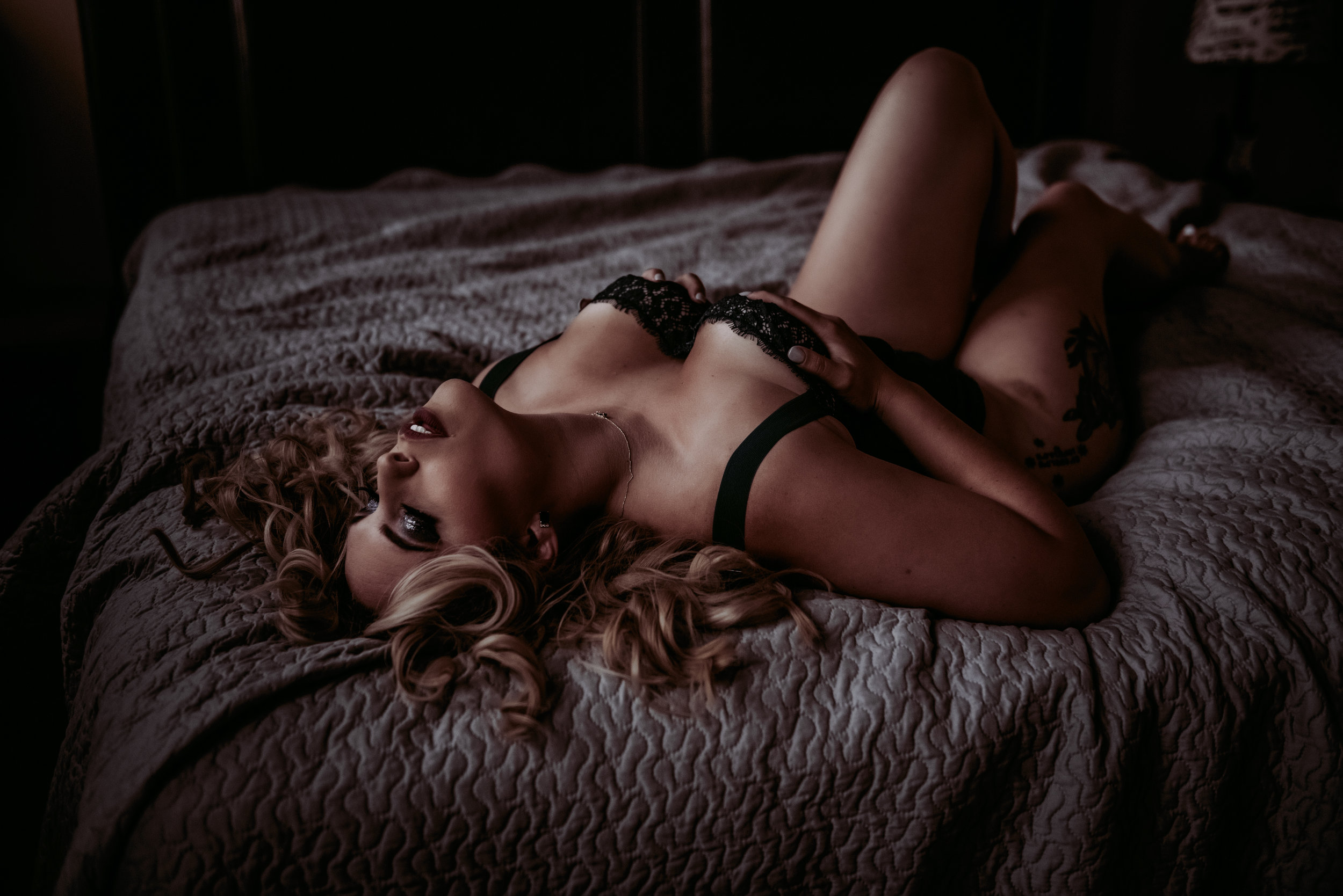 Blonde laying on bed in black body suit boudoir photography new york city studio