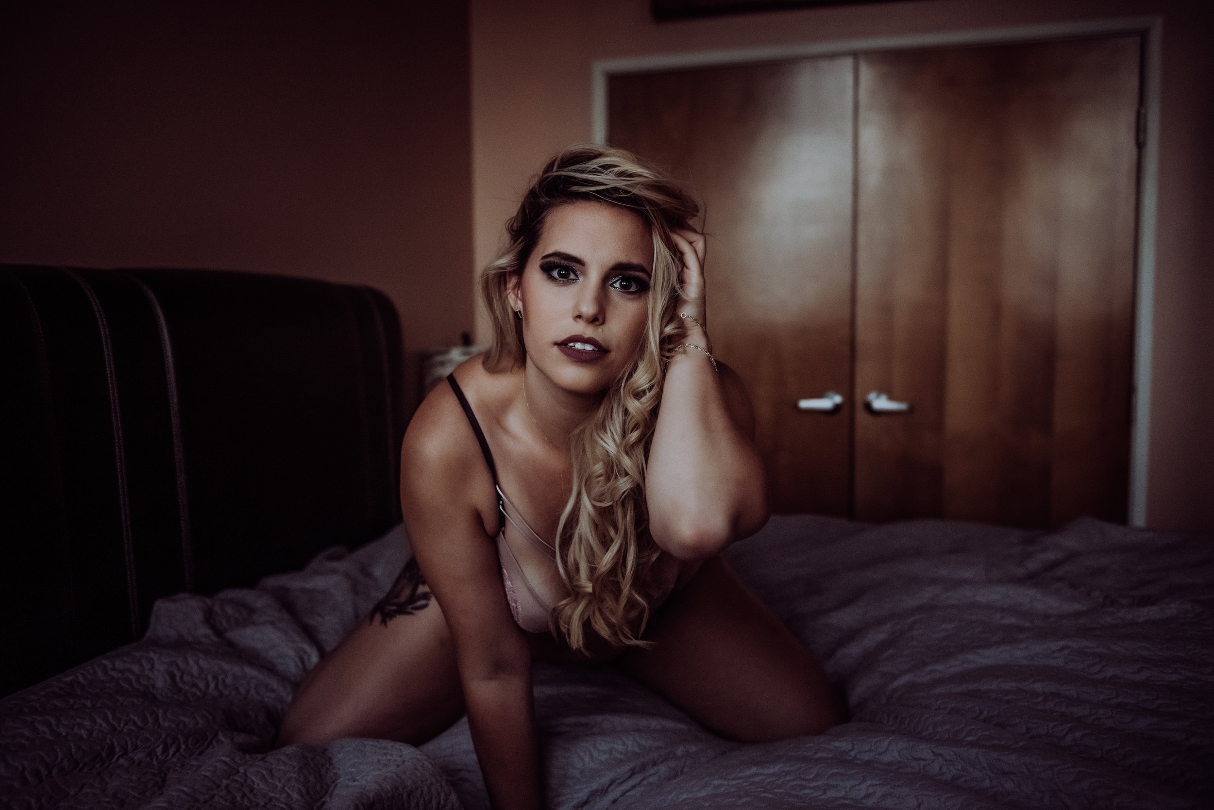 Blonde with hand in hair sexy kneeling on purple sheets  boudoir photography new york city bedroom