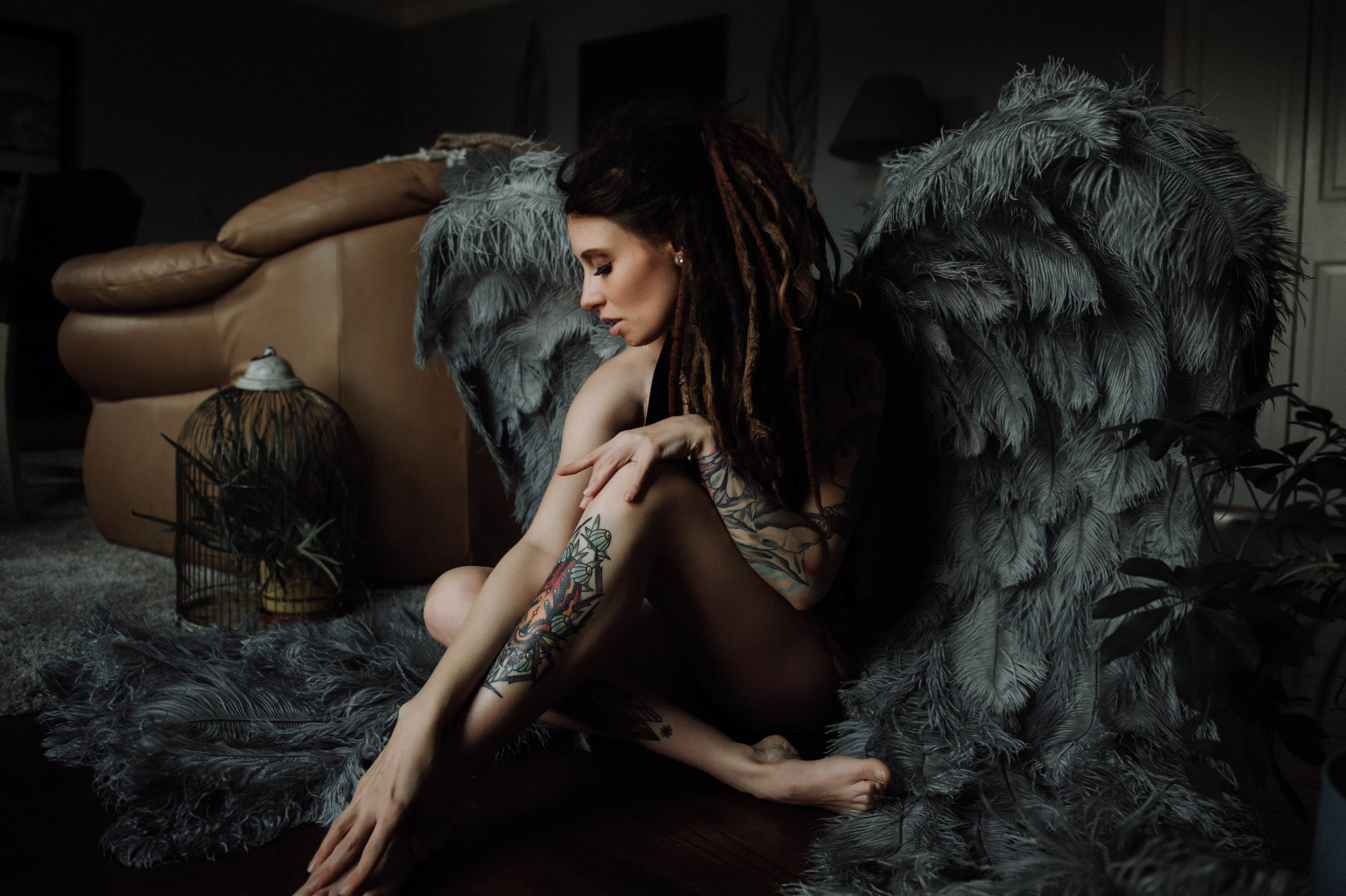 Tattooed model with dreads wearing gray angel wings  boudoir photography new york city bedroom