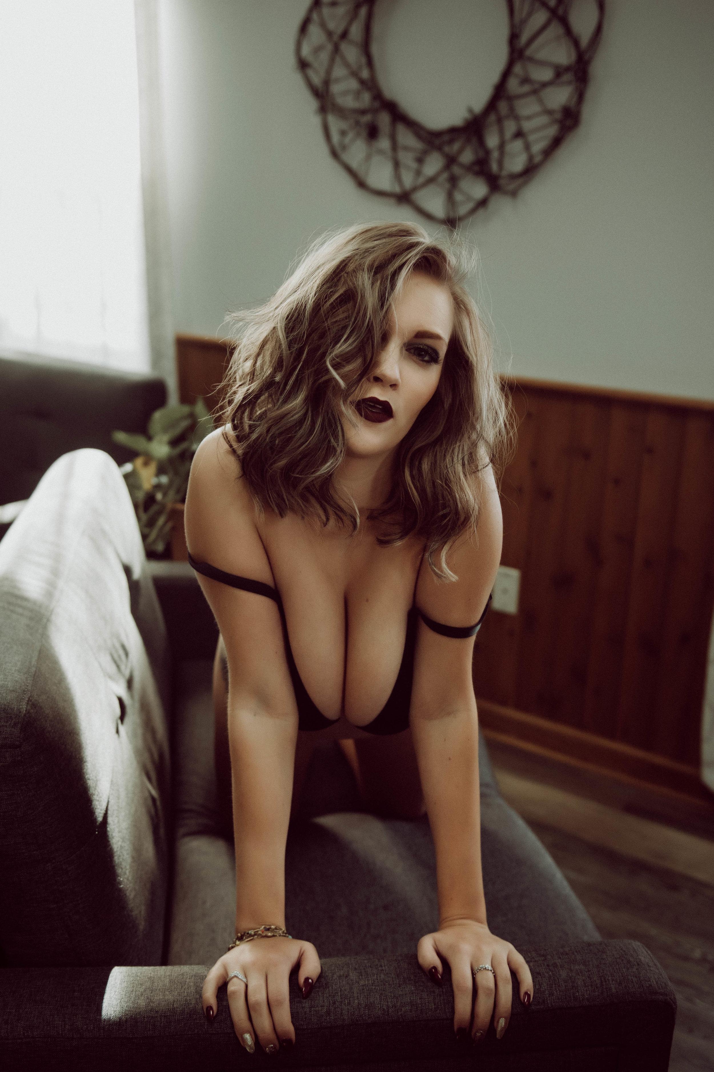 short hair woman kneeling on couch in black bra boudoir photography new york city studio