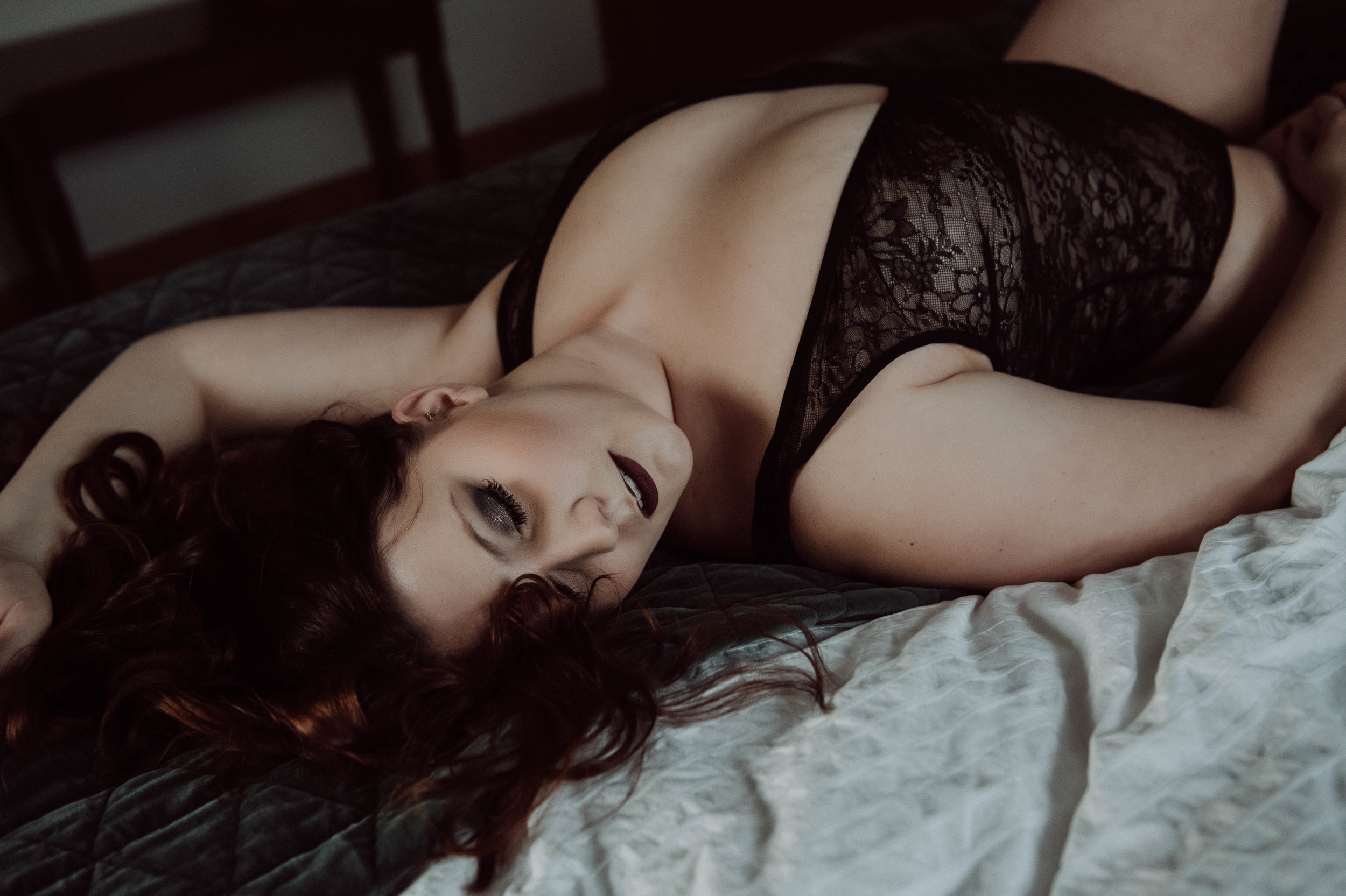 Brunette laying on bed in black body suit sexy  boudoir photography new york city bedroom