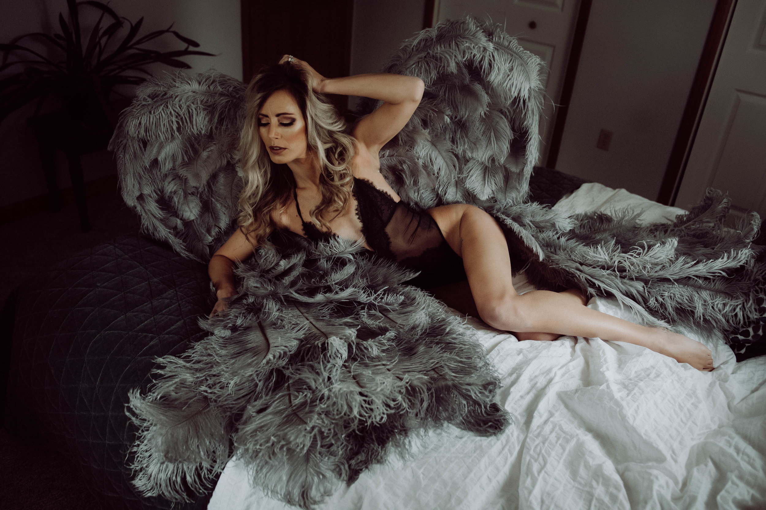 Blonde woman in black bodysuit gray angel wings  boudoir photography new york city bedroom