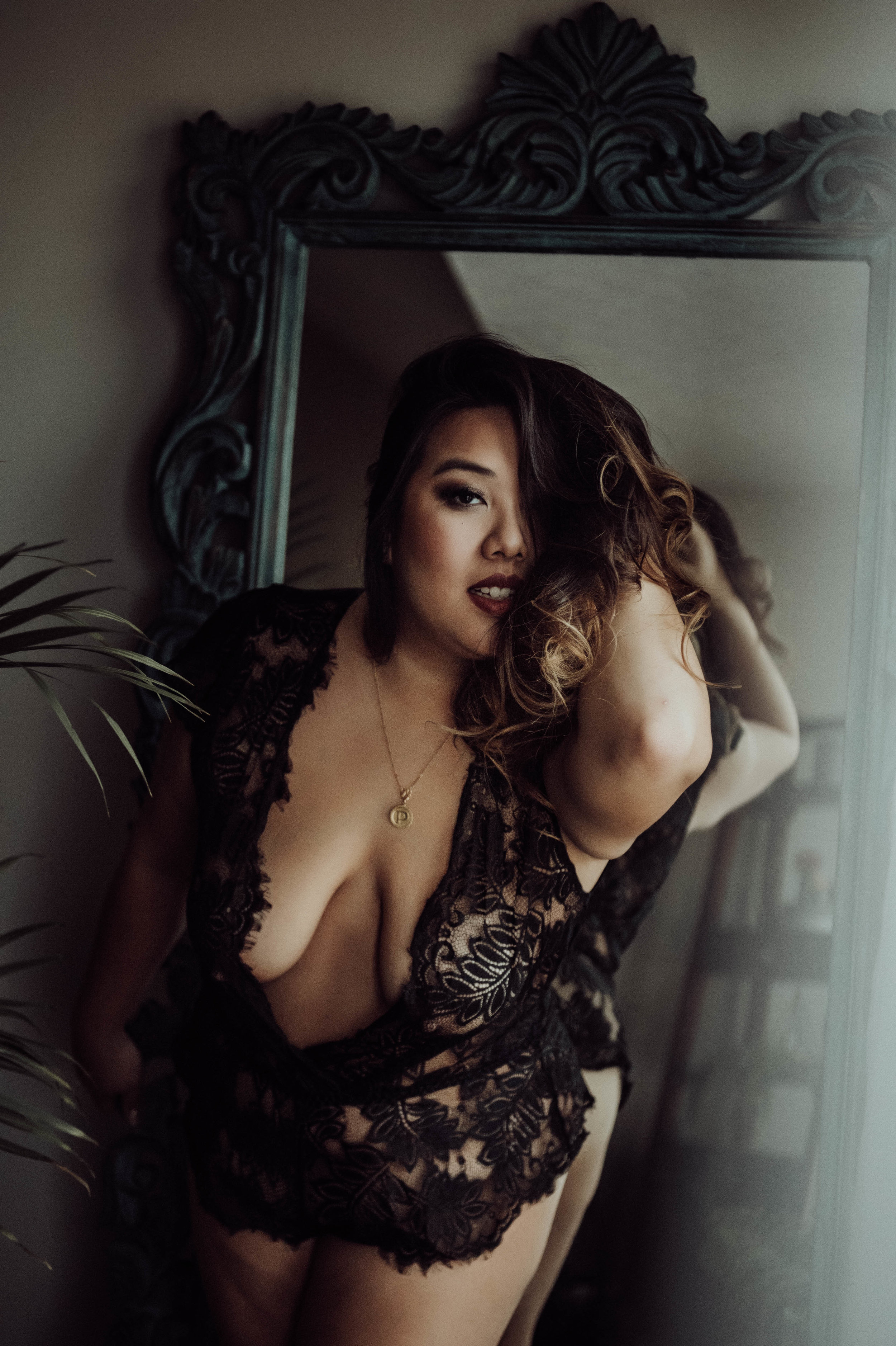Plus size asian woman in black lace lingerie standing with mirror boudoir photography new york studio