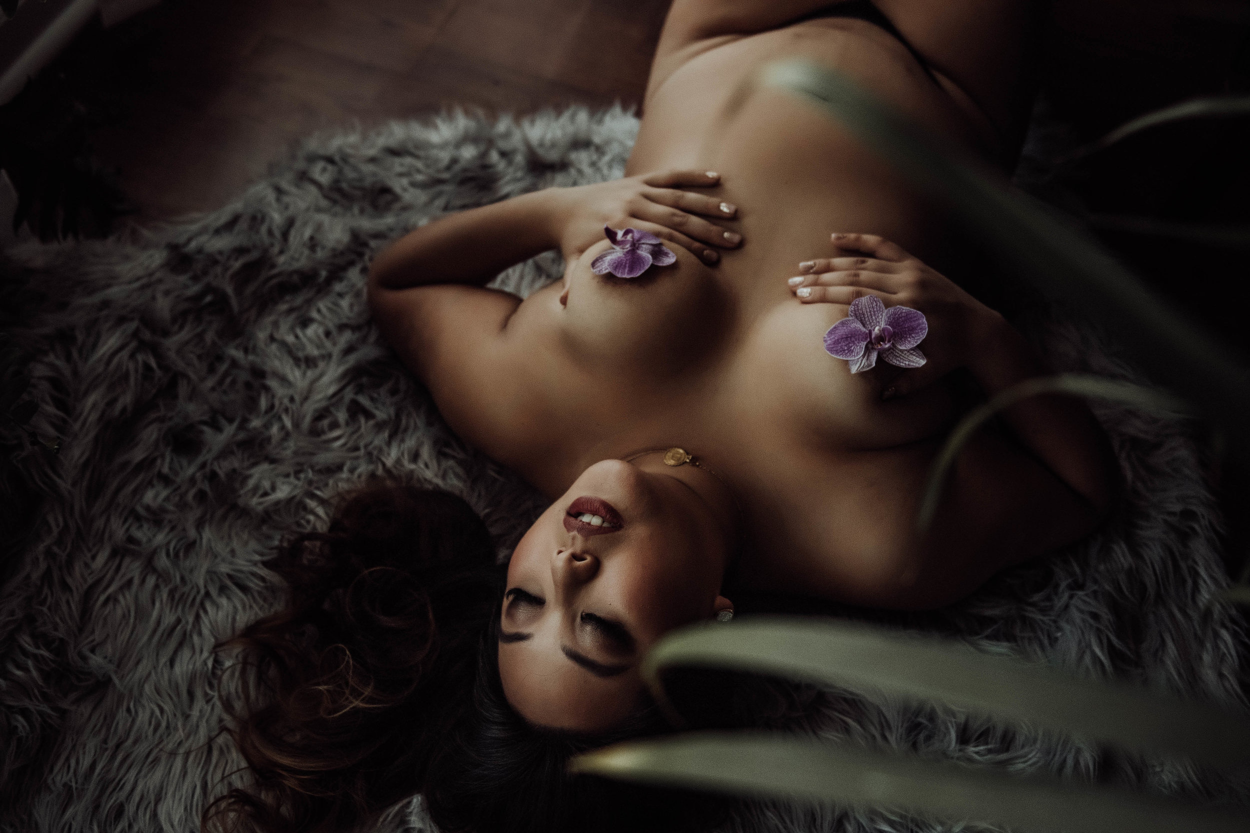 Nude Plus size asian woman laying on fur rug with flowers boudoir photography new york studio