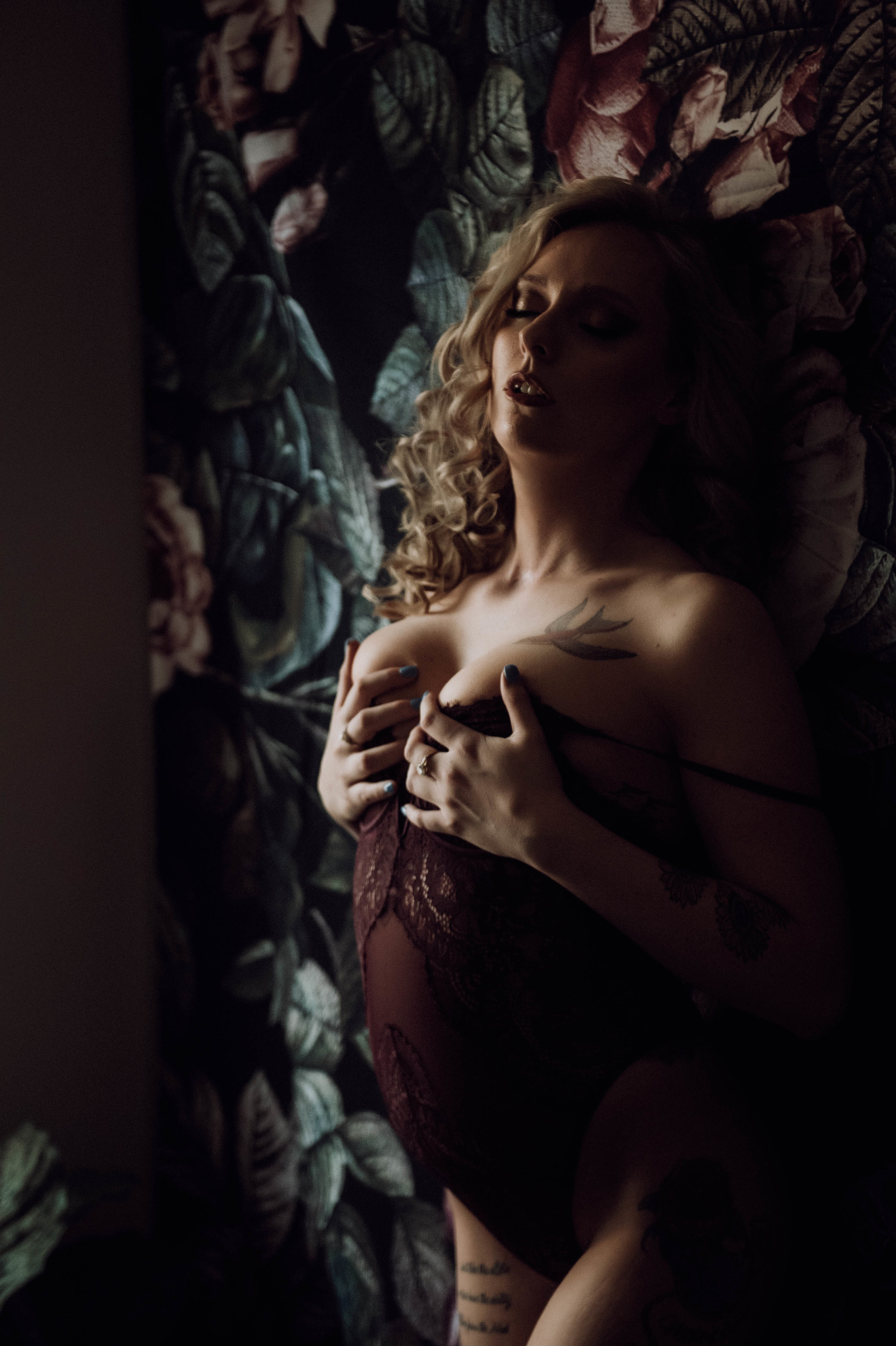 Curly hair blonde woman in purple lace bodysuit flowers on wall boudoir photography new york city studio