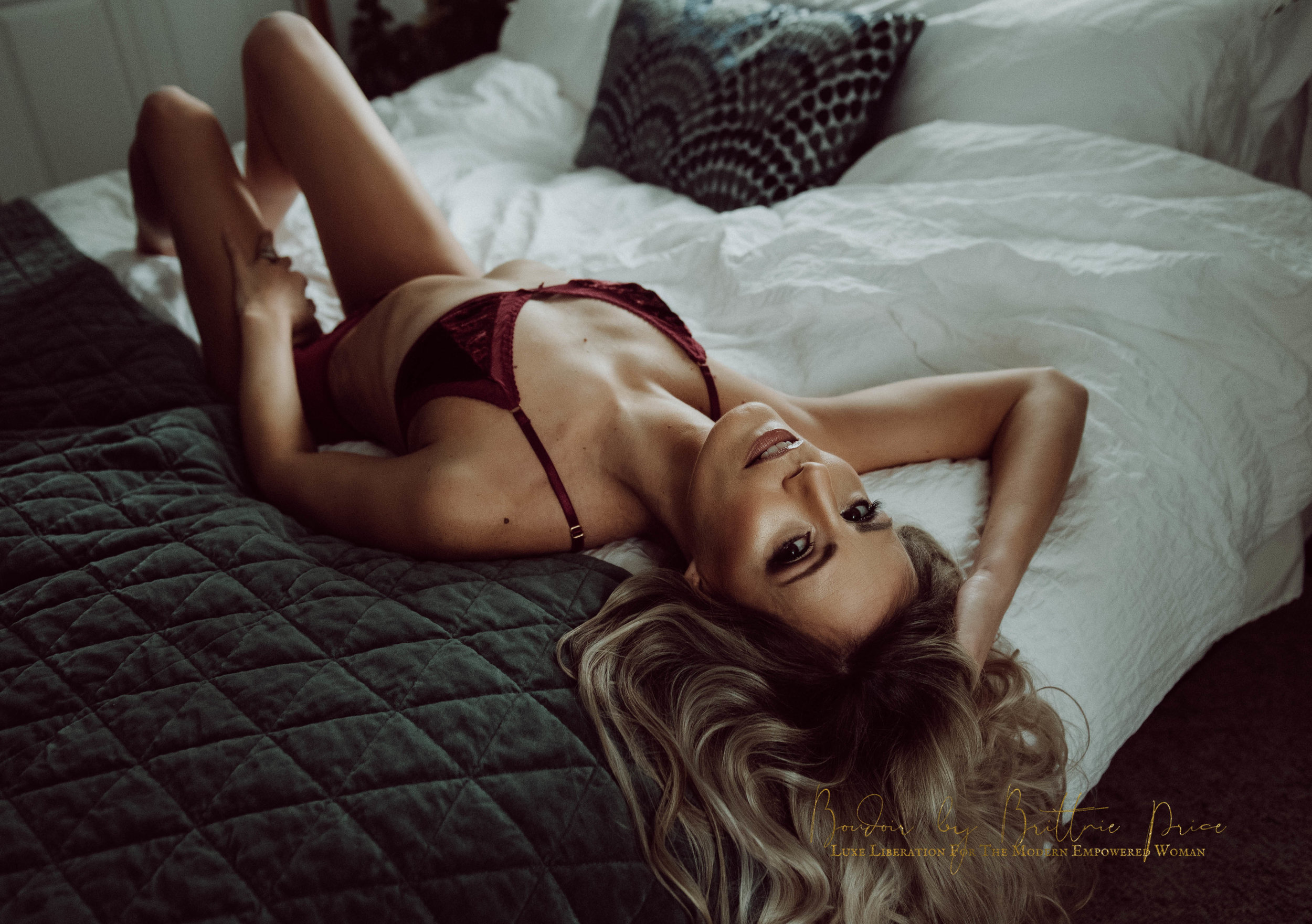 Blonde woman laying on bed in red bra and underwear boudoir photography new york studio