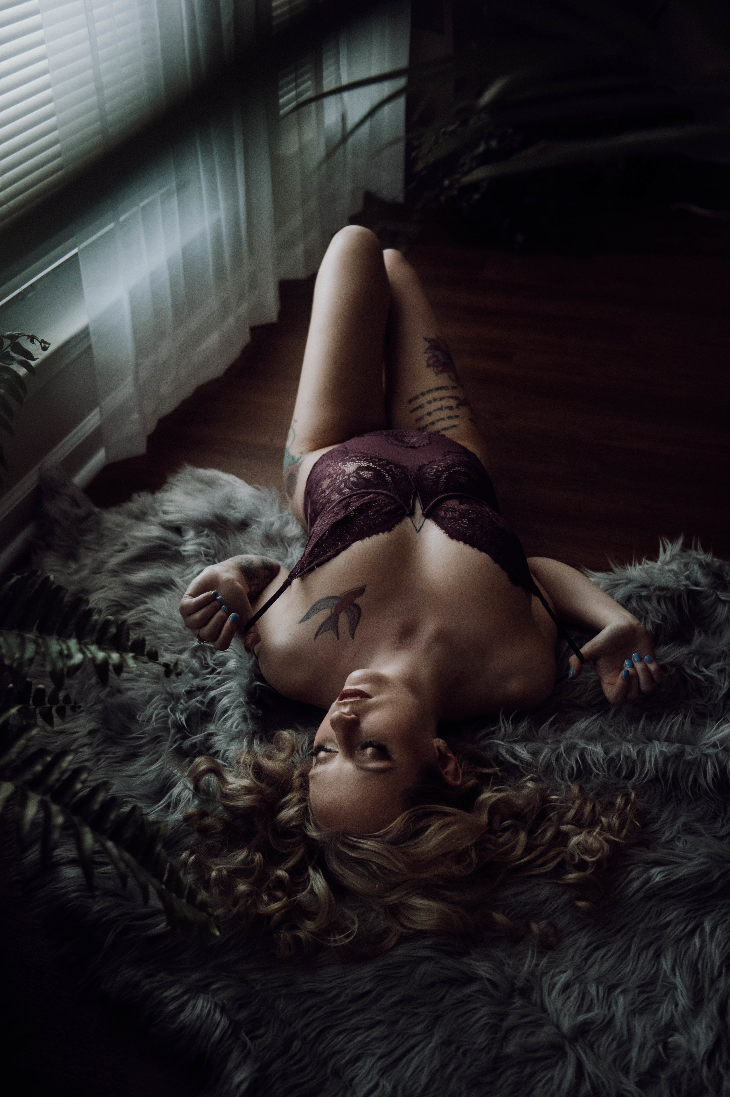 Blonde laying on gray rug in purple lace bodysuit boudoir photography new york city studio