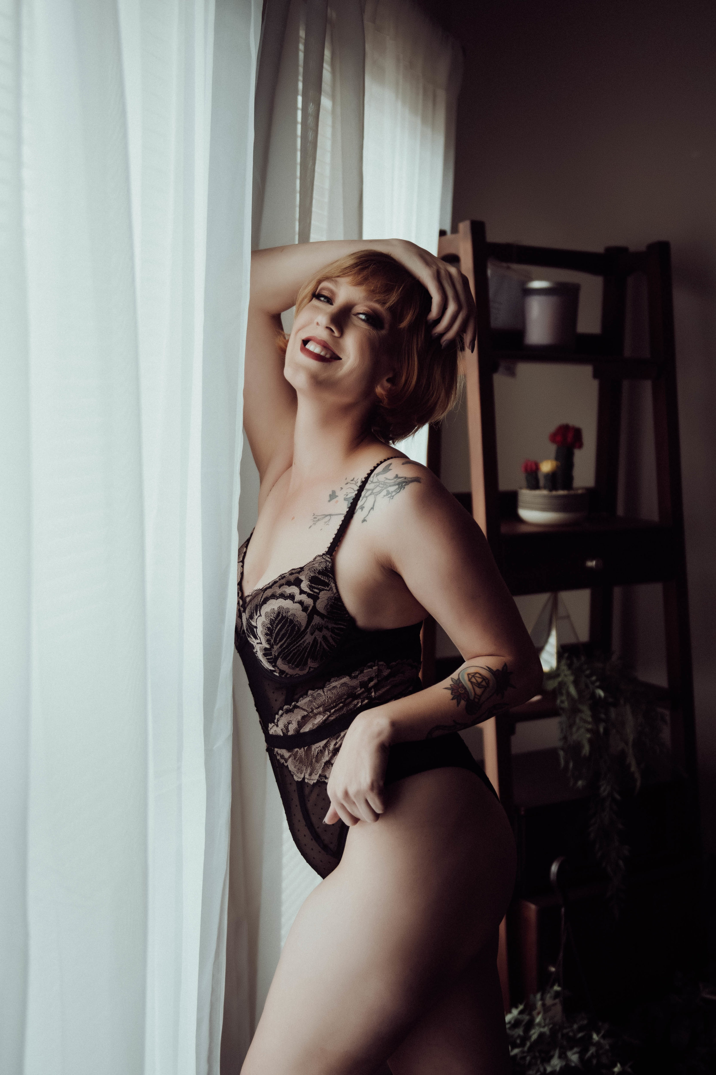 Smiling short hair woman redhead in black lace bodysuit boudoir photography new york city studio