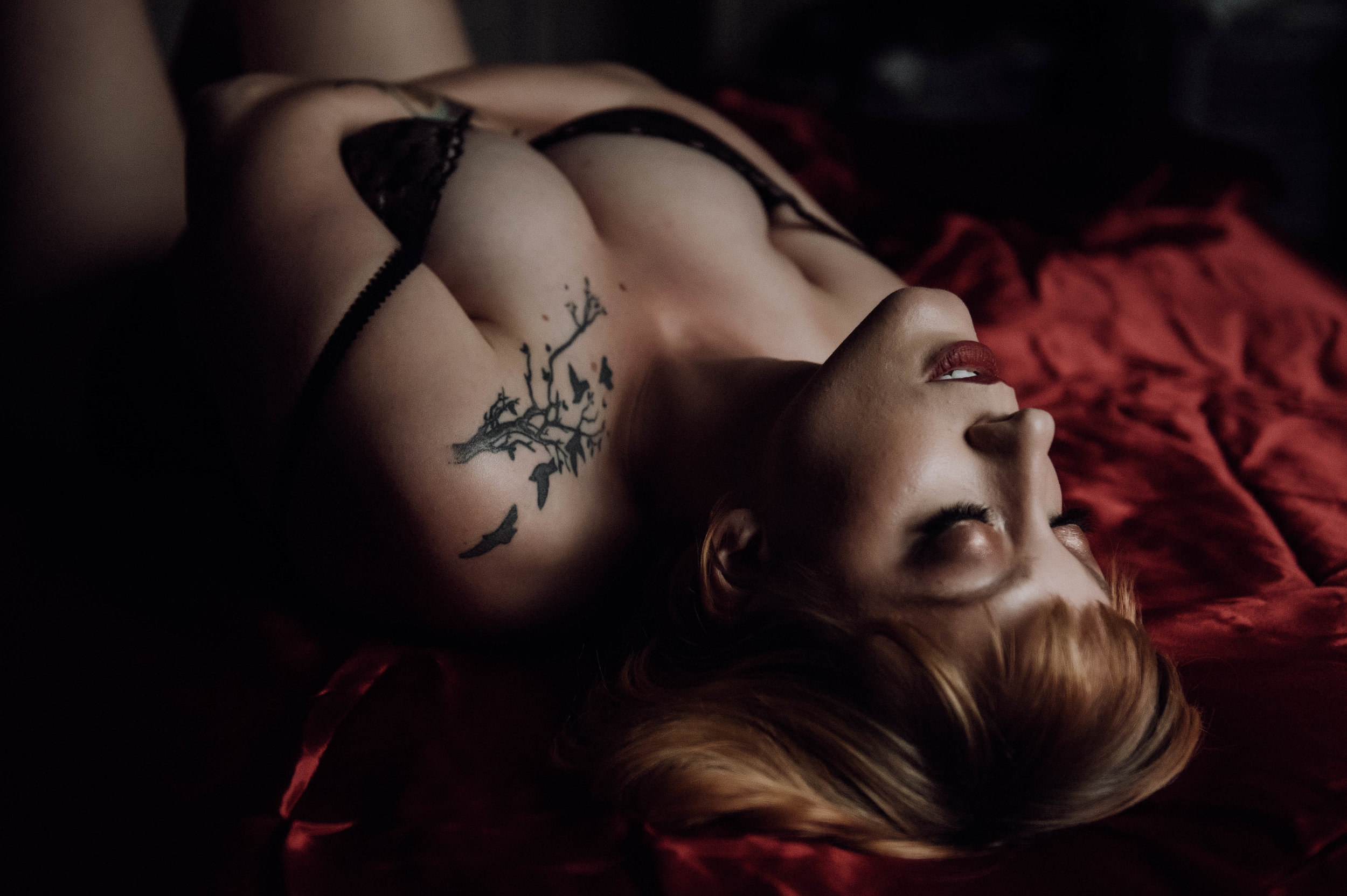 Redhead woman laying on red sheets in black lace bodysuit boudoir photography new york city studio