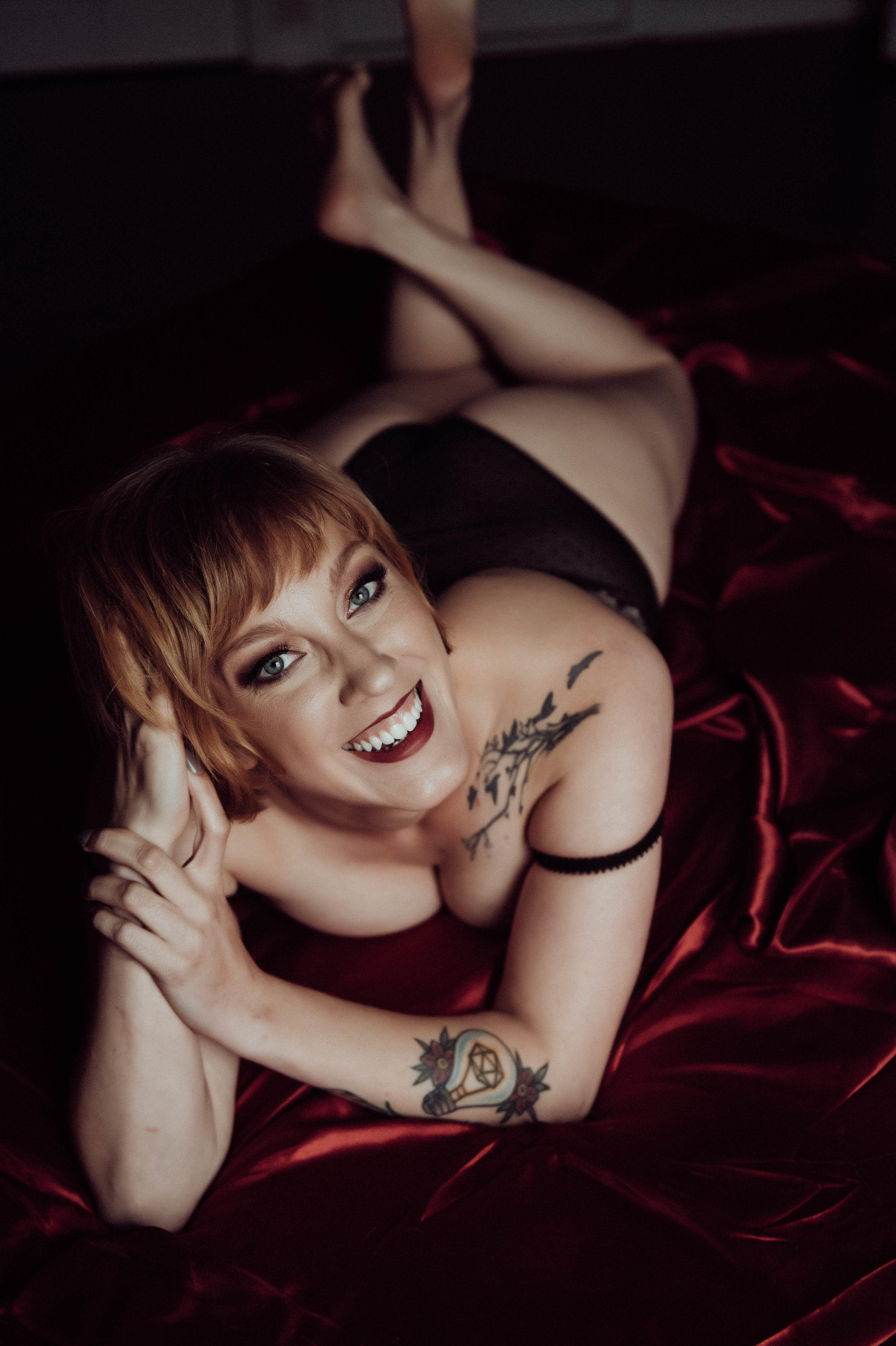 Smiling redhead woman on red sheets laying on stomach lace bodysuit boudoir photography new york city studio