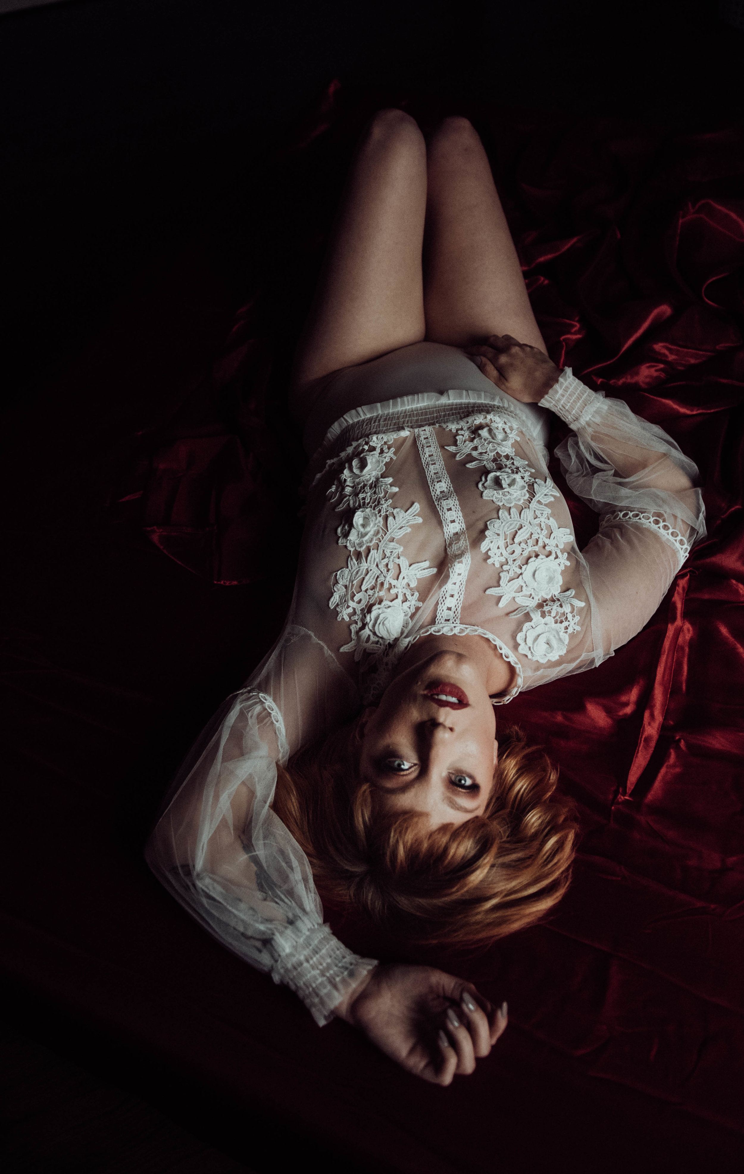 Redhead with blue eyes laying on red sheets in white lace bodysuit boudoir photography new york city studio