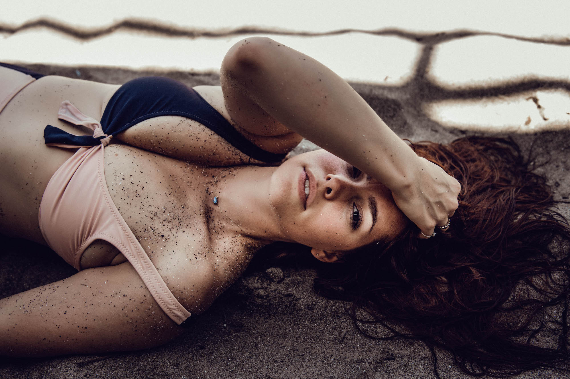 Brunette woman in bathing suit laying down intimate boudoir photography New York City outdoors
