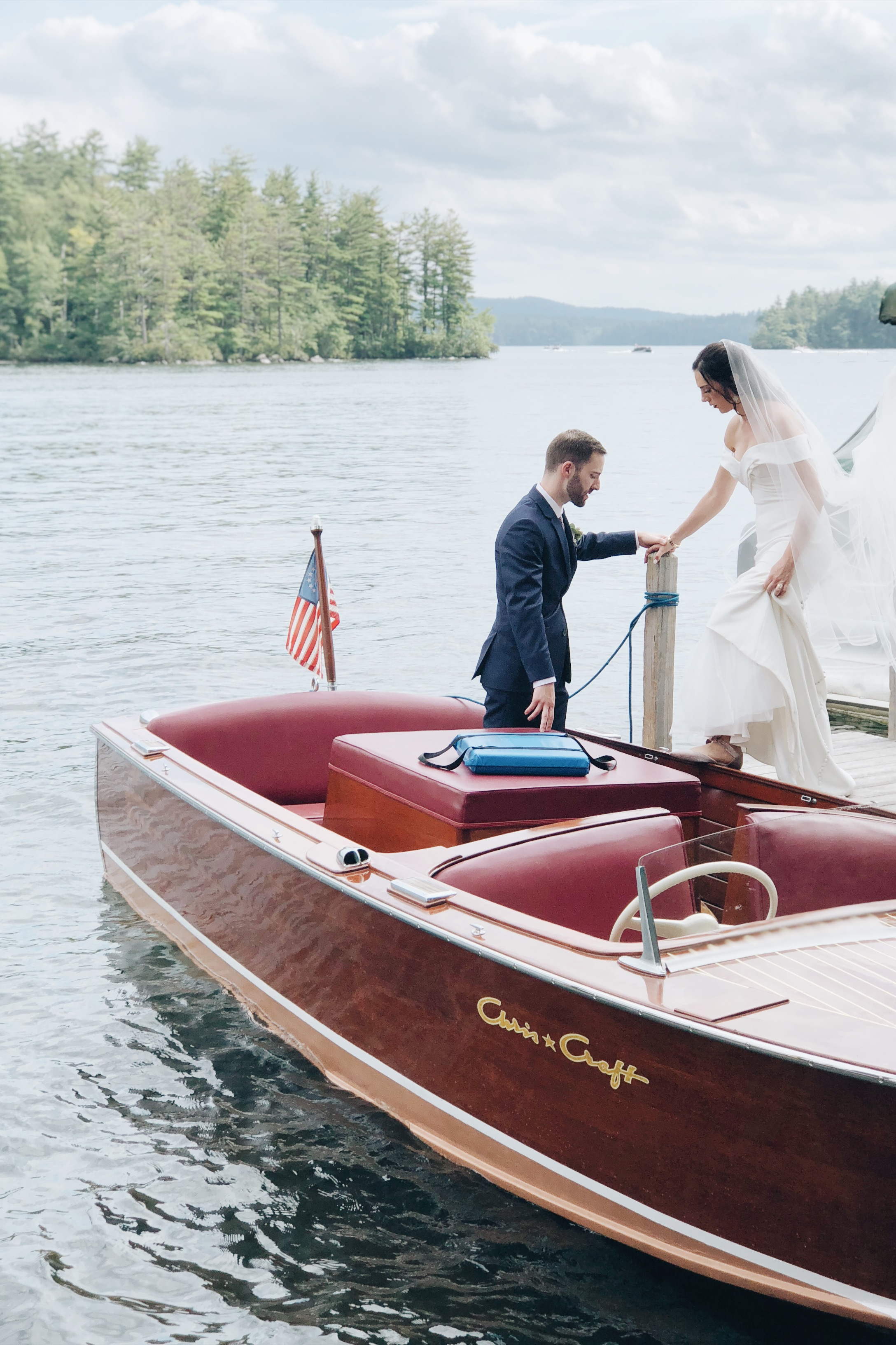 Bride and groom leaving Church Island in a wooden boat