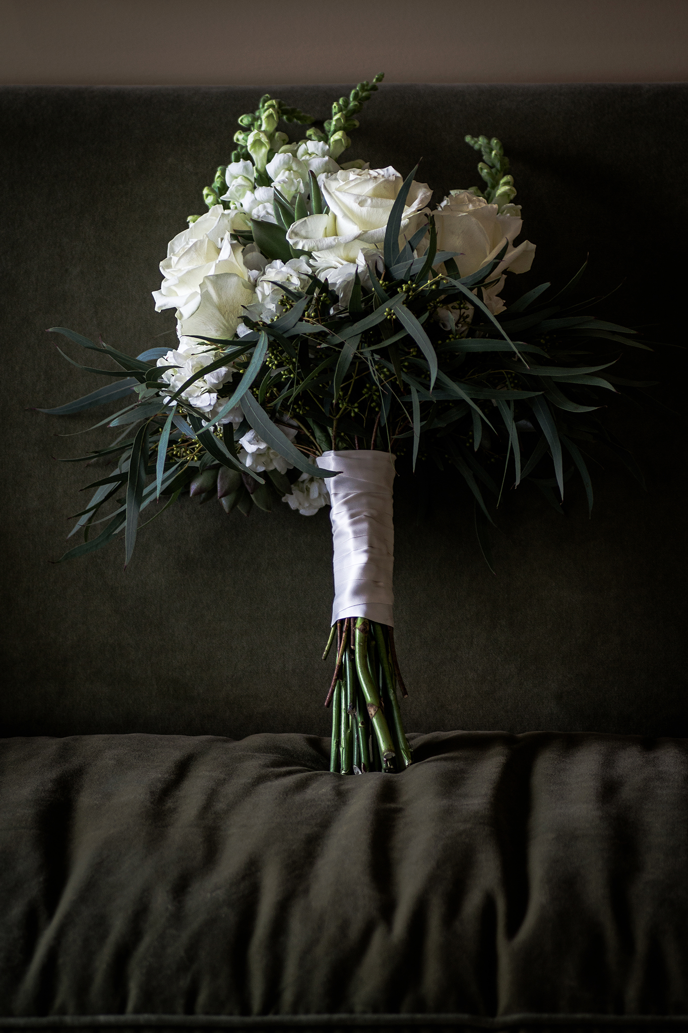 bridal bouquet on green velvet couch