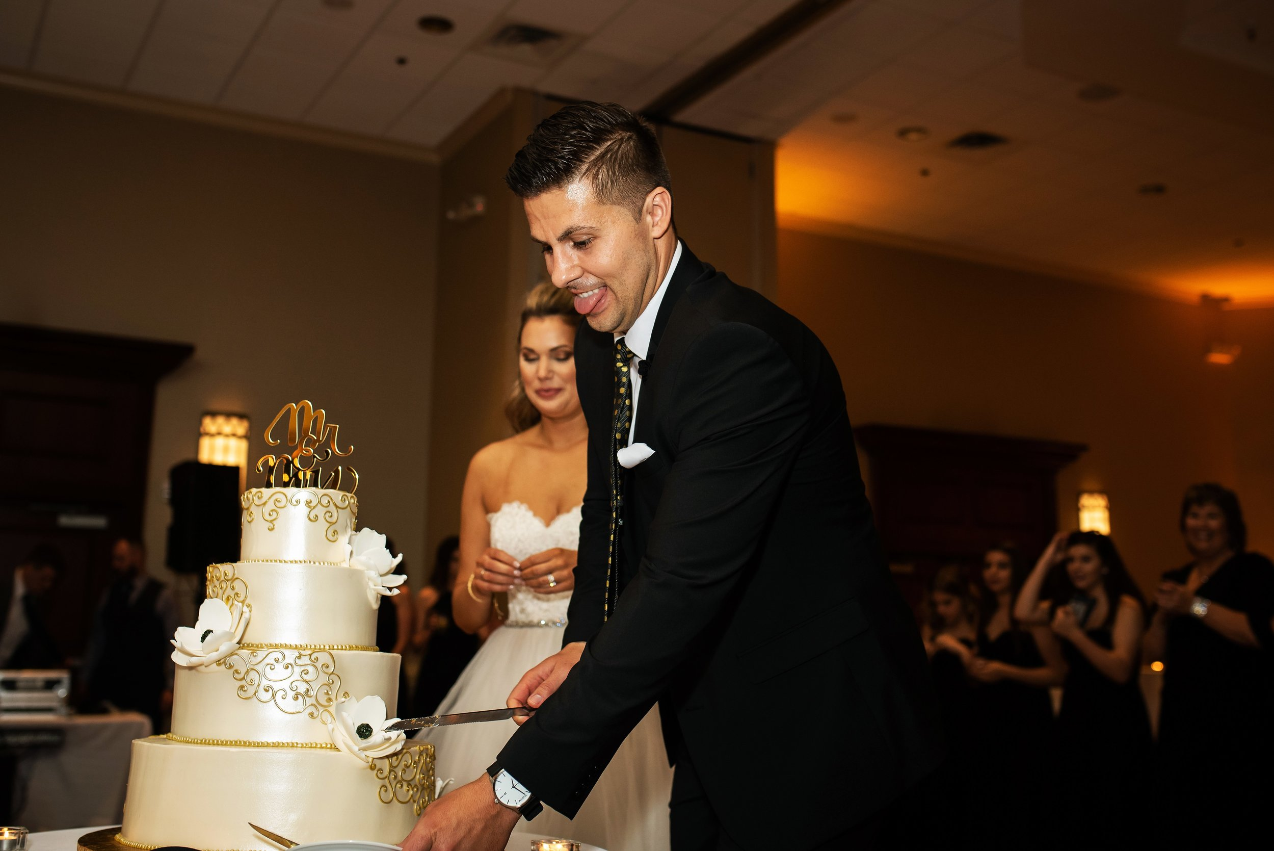 Groom Sticks out tongue as he cuts wedding cake
