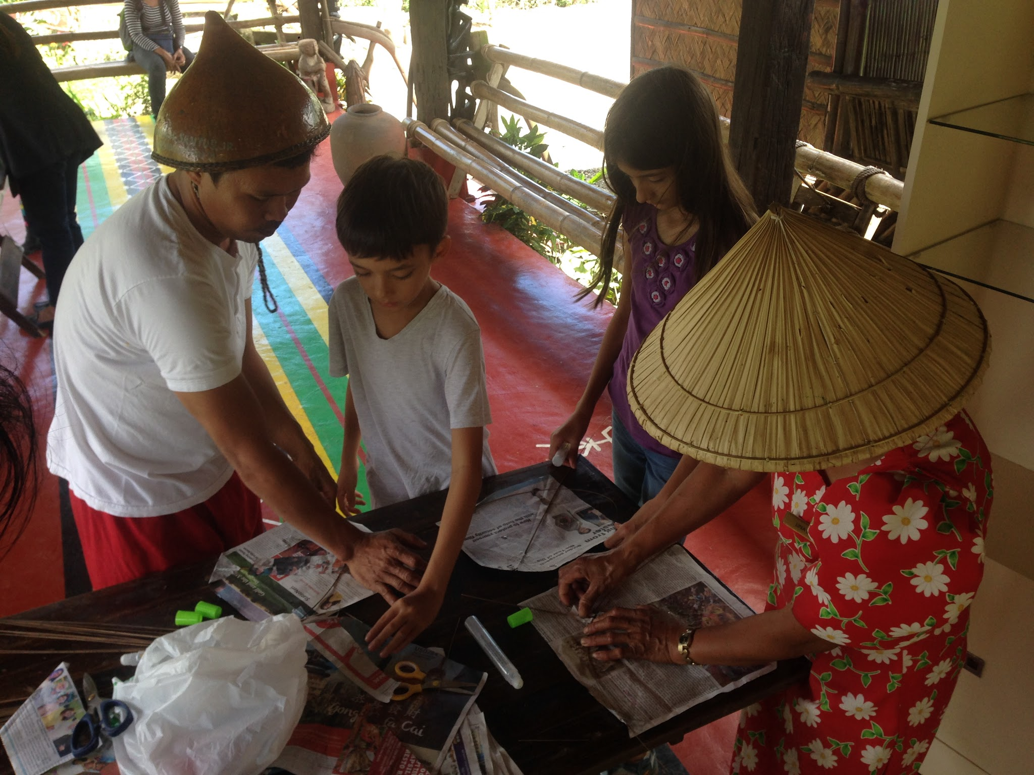 Making kites from newspaper, long twigs, glue and thread