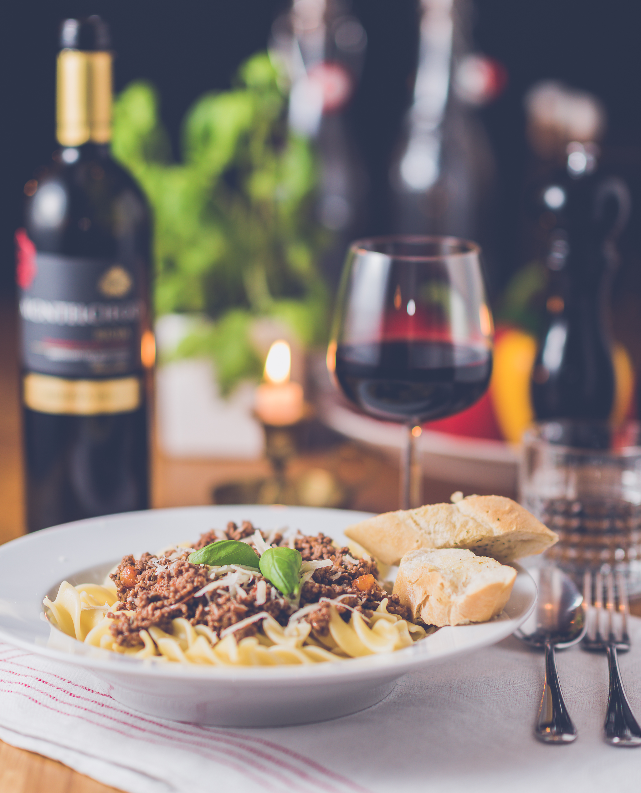 romantic meal including a pasta dish and glass of wine