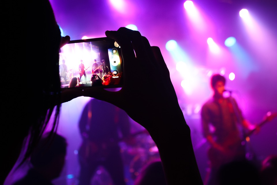 person filming concert