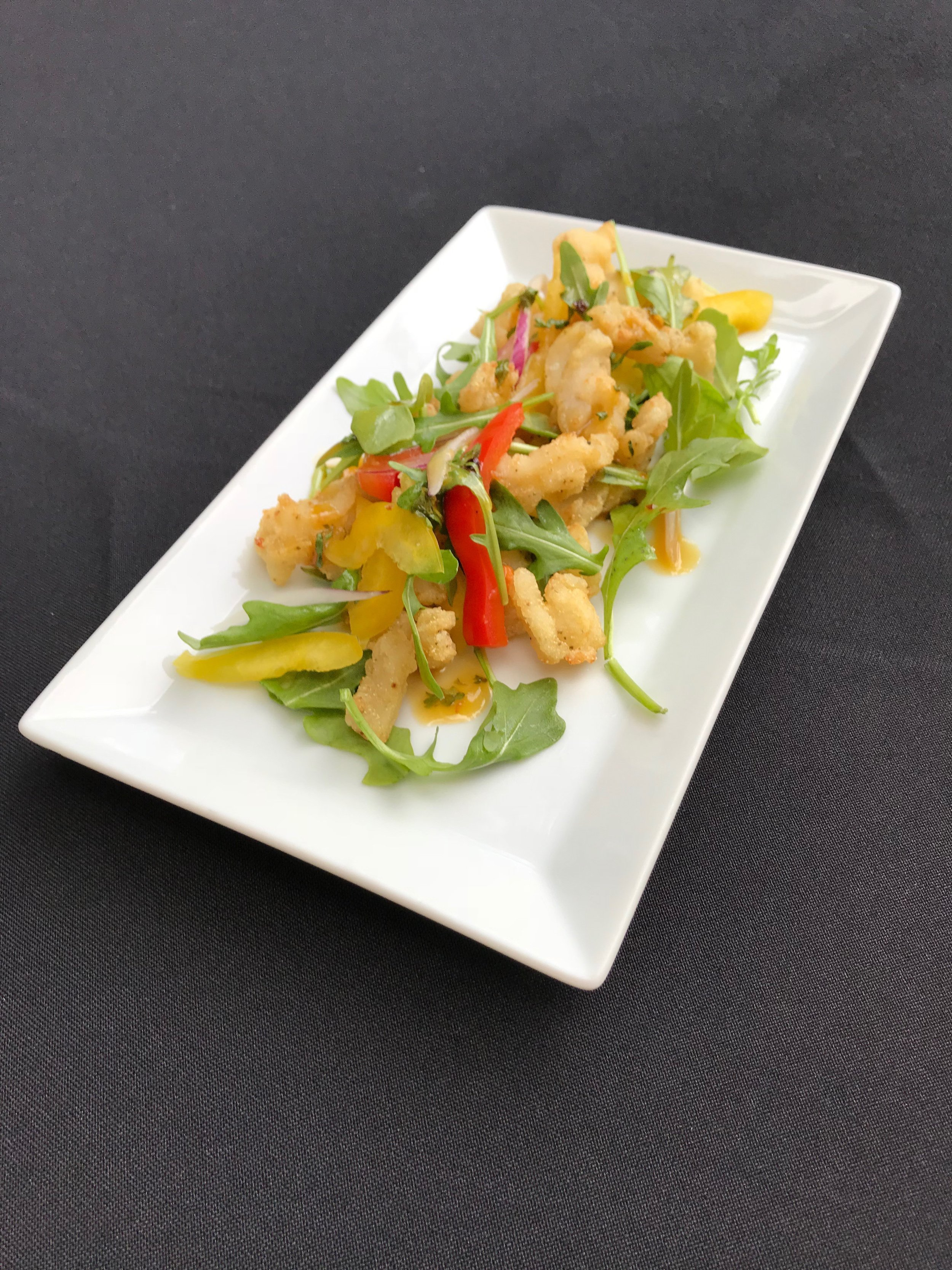 Conch Salad - Fresh conch, thinly sliced and deep-fried, served with bell peppers, arugula, red onion, and dressed with a sweet orange sauce