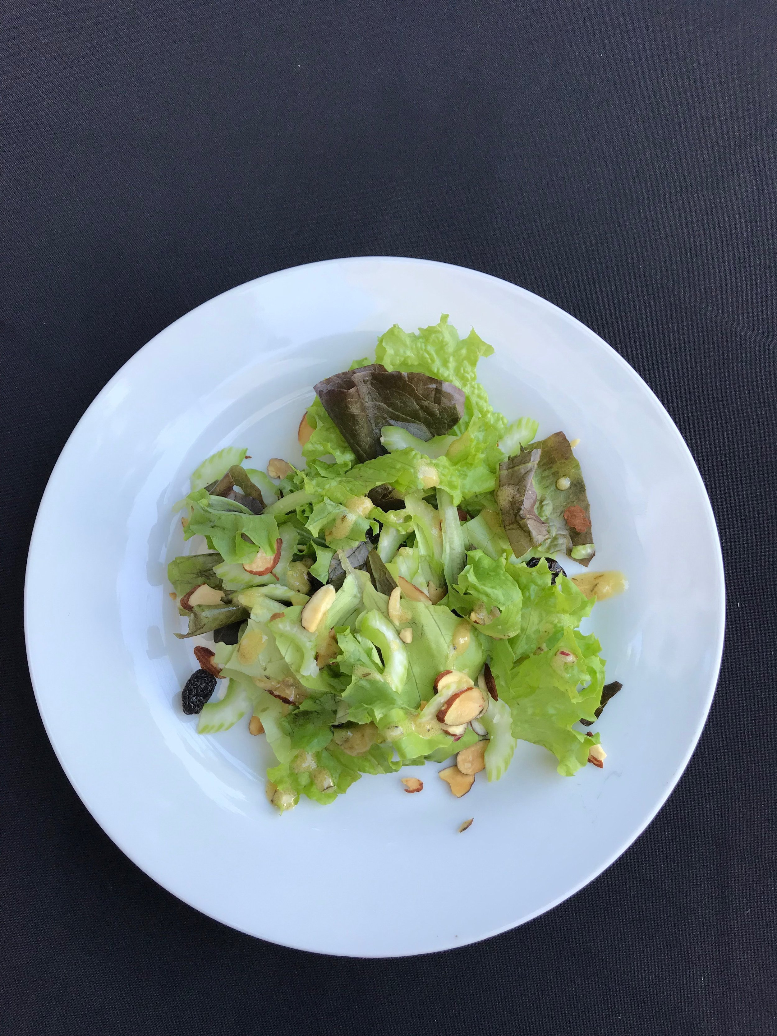 Baby-Greens Salad with Toasted Almonds - Mixed greens with shaved celery, toasted almonds, and raisins, dressed with Dijon whole mustard vinaigrette