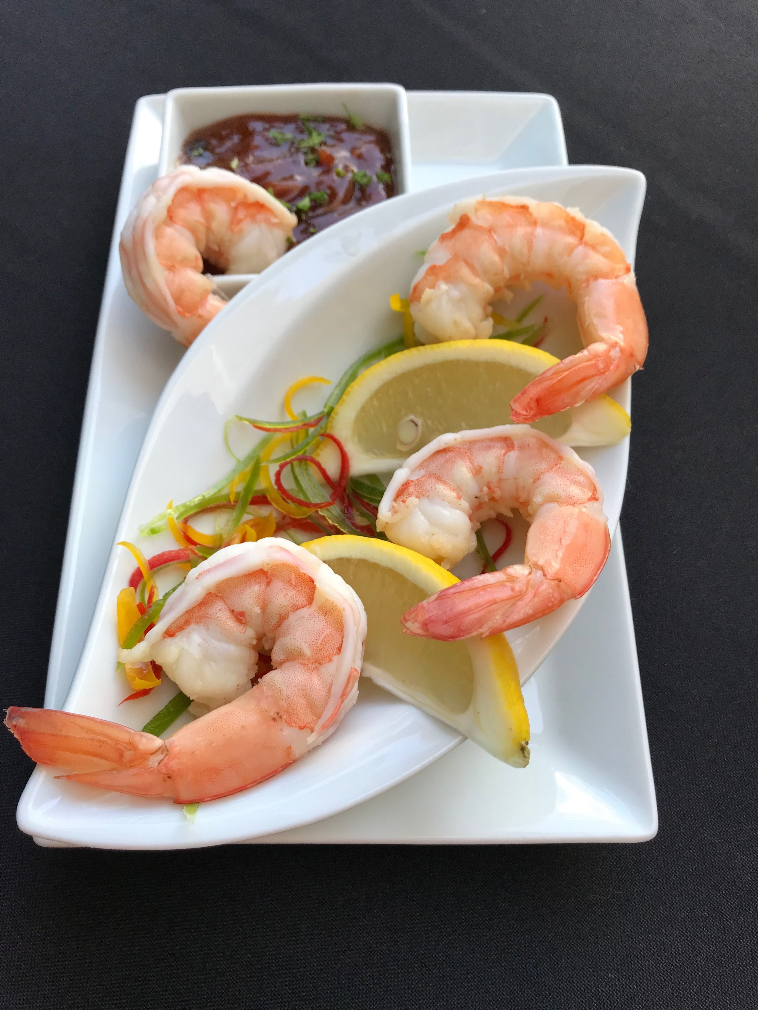 Shrimp Cocktail - Shrimp, poached in stock flavored with celery, onions, carrot, bay leaf, parsley & thyme, and served with horseradish cocktail sauce