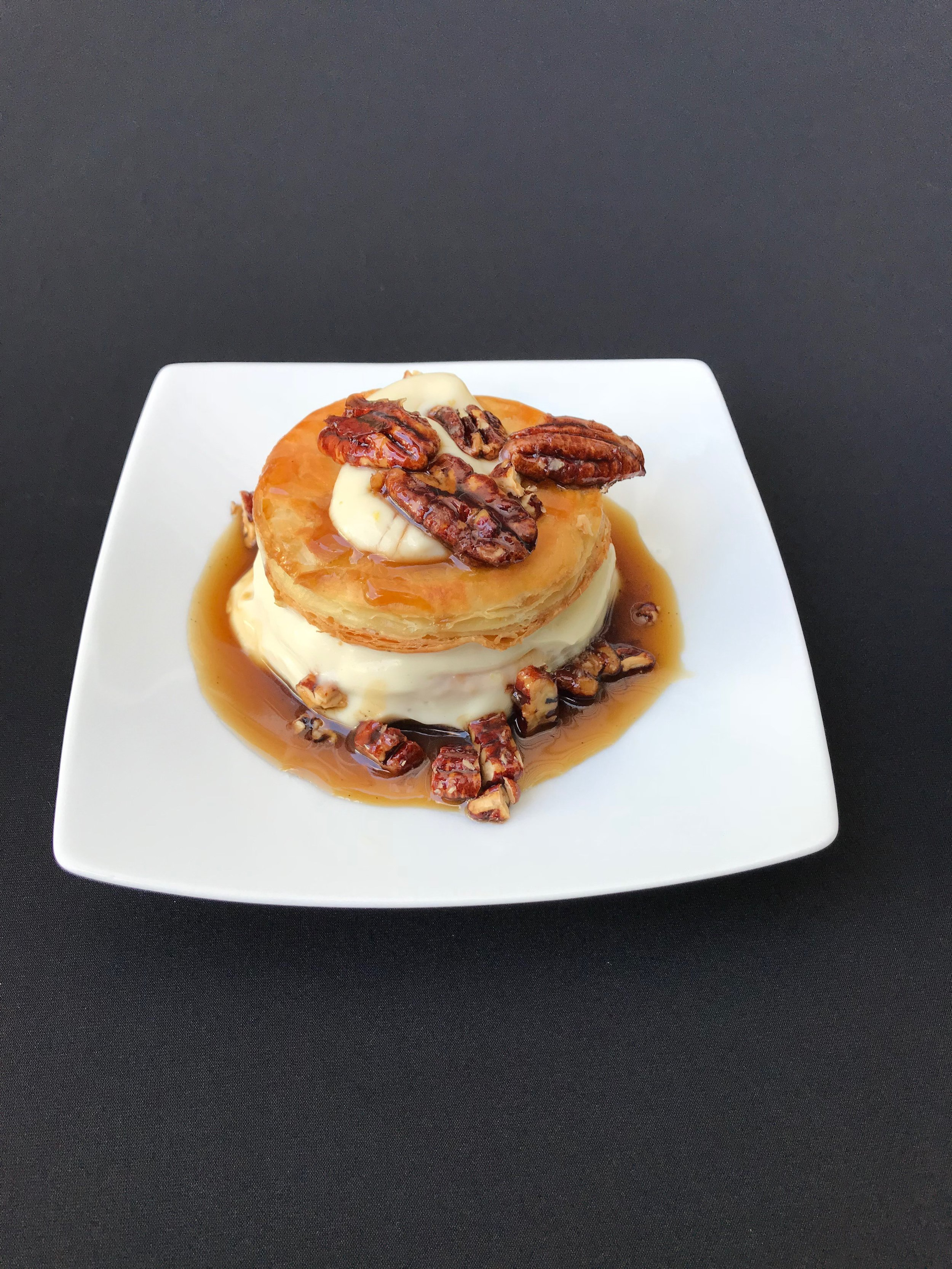 Puff Pastry Soufflé - Baked puff pastry dough with orange scented cream filling, caramel butter sauce, and candied pecans