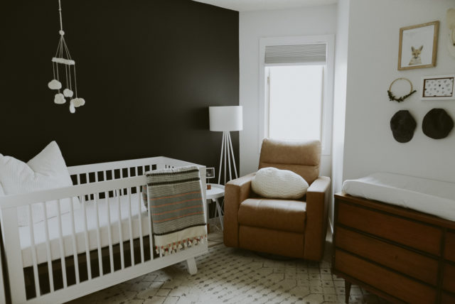 eclectic nursery with dark feature wall