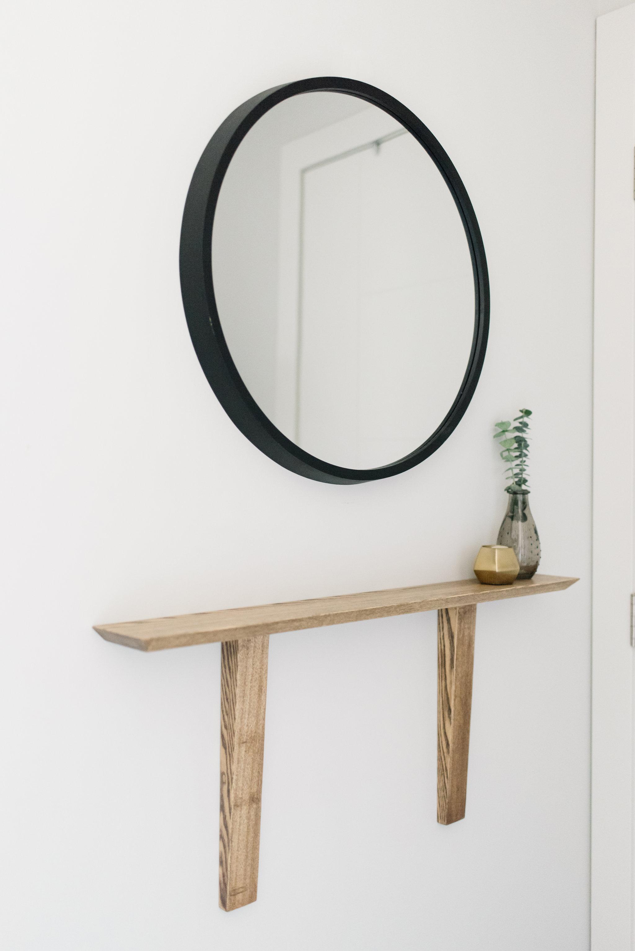 round mirror and small ledge shelf