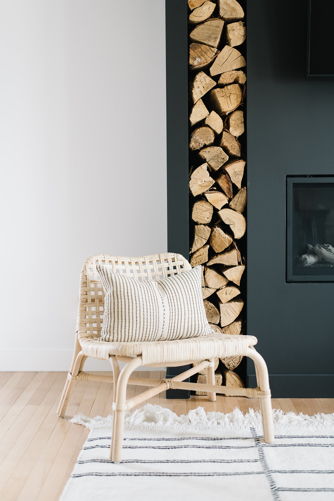 black fireplace with vertical wood storage