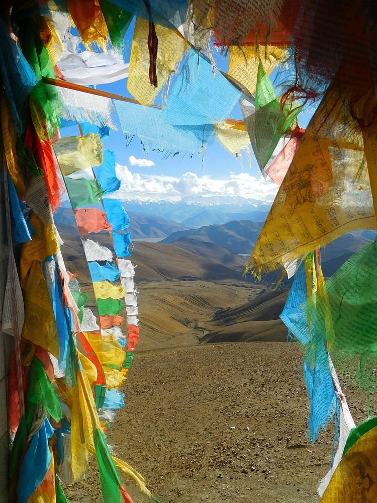 A view toward the Himalayas peeks through multitudes of prayer flags.