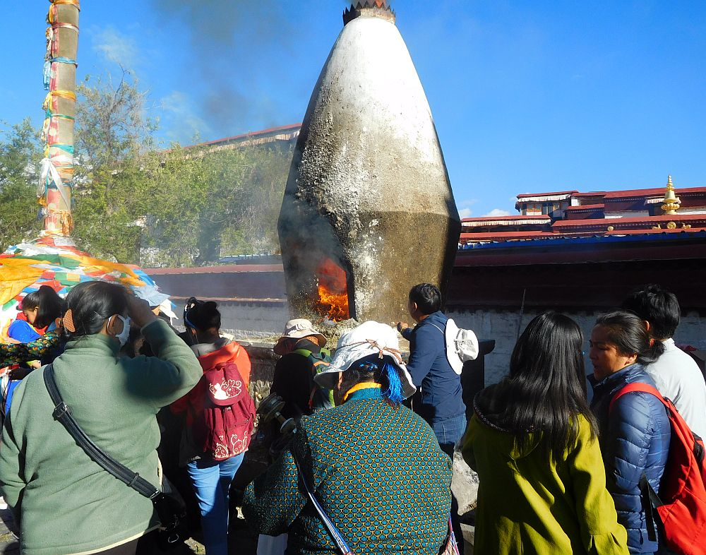 Worshippers throw incense into the stupa as they pass by on the kora in Lhasa.