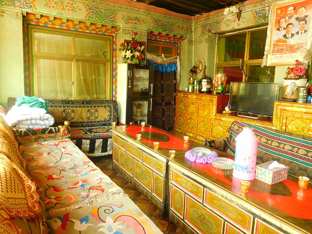 Living room of a traditional Tibetan family's home, complete with Chinese leaders' portraits.