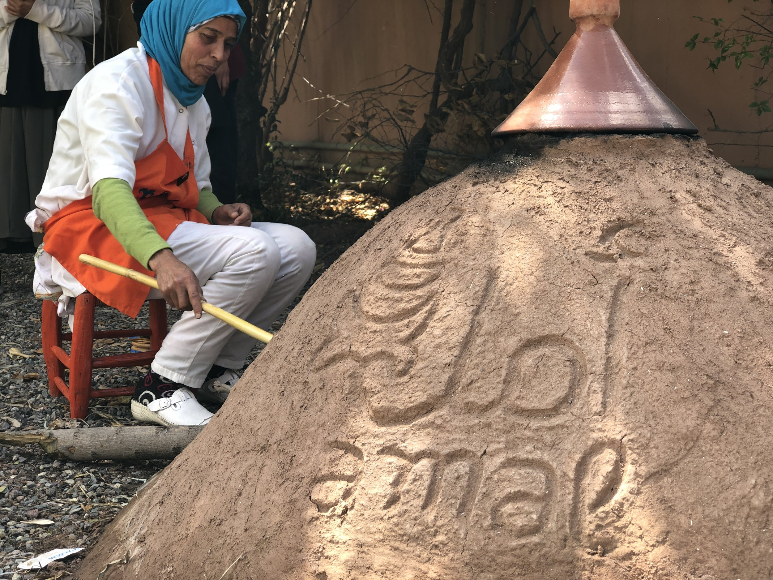 Fatiha stokes the fire in the clay bread oven in the garden at Amal Targa.