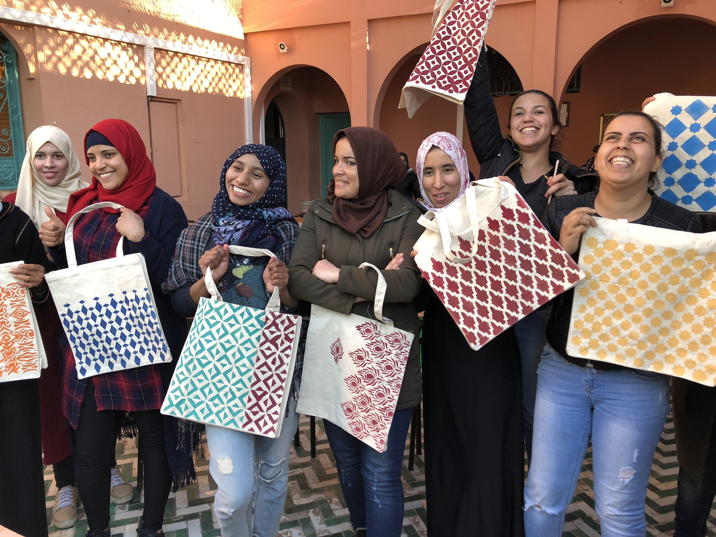 The new cohort of trainees show off the school bags they painted with a visiting art teacher.
