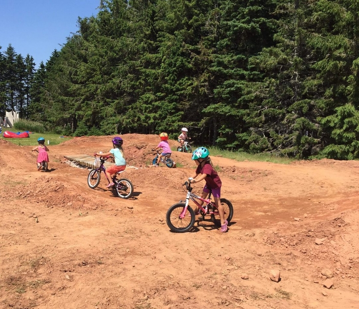 The girls with their friends biking on the BMX track at camp.