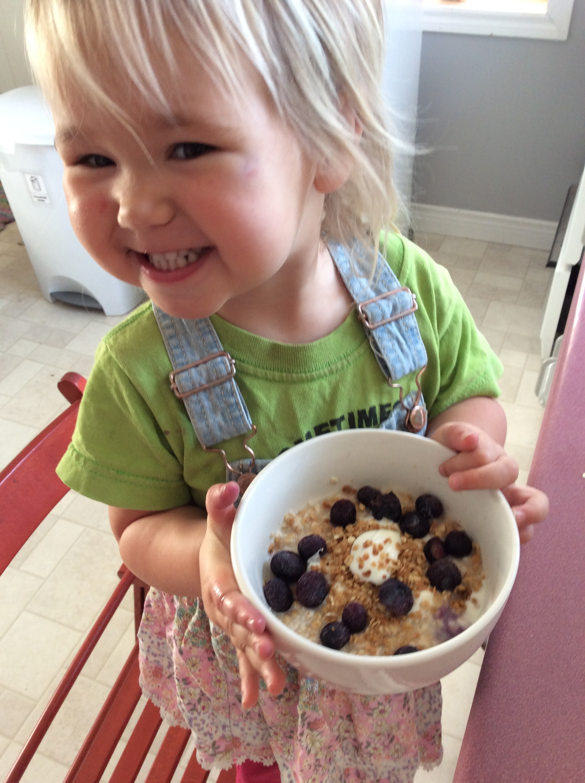 Sprout #4 is thrilled with her breakfast of cooked oatmeal—topped with frozen blueberries, yogurt and granola.