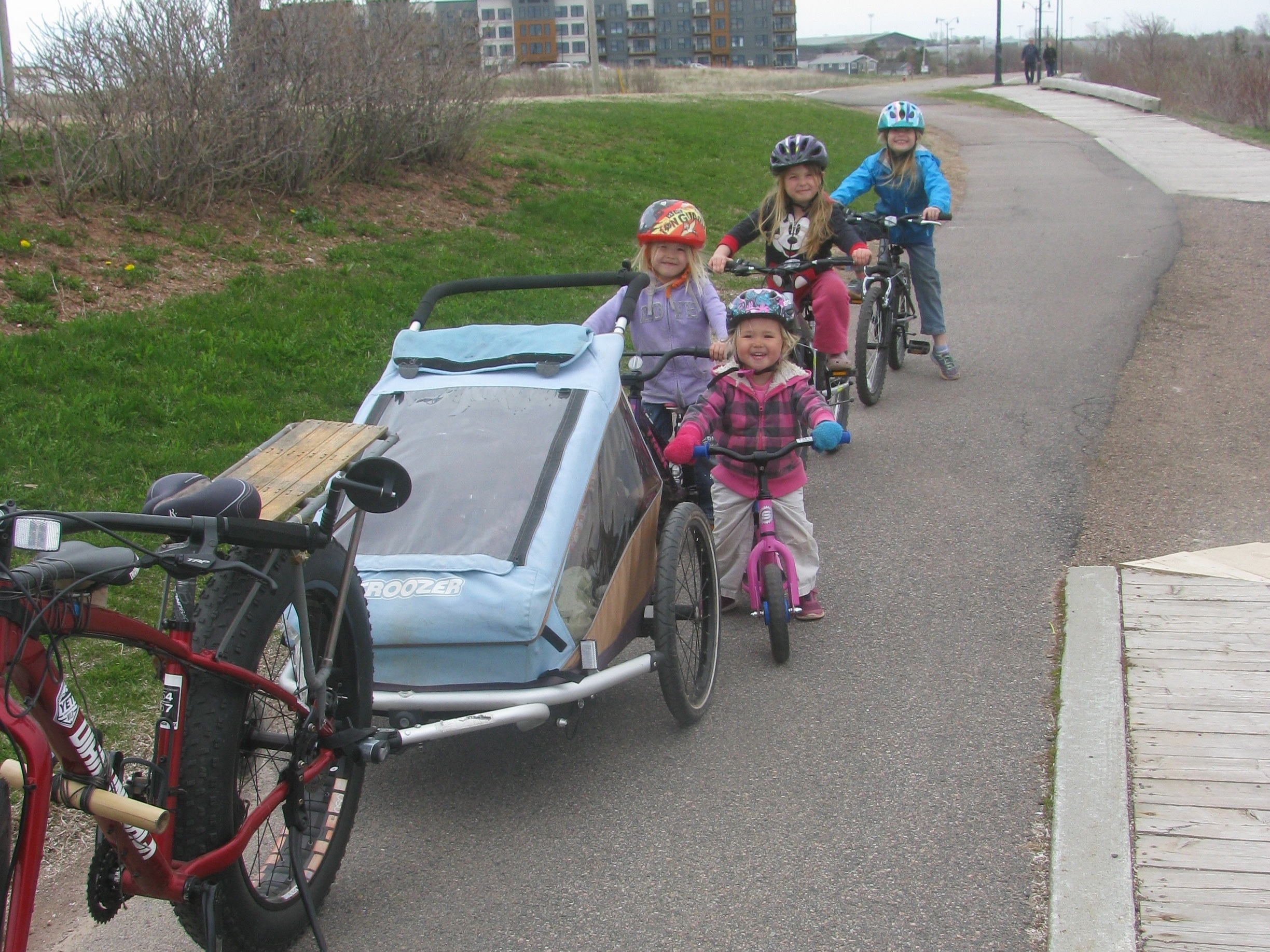 Enjoying a bike through town on a bike/walking path. Sprout #4 trades off riding her balance bike with riding in the trailer with her little sister.