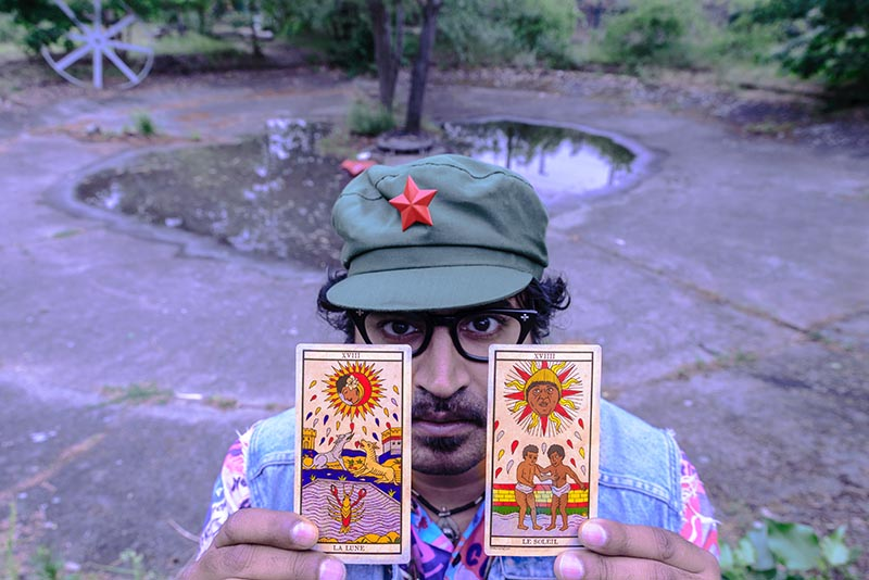 Arish Khan posing with The Moon and The Sun cards from his Black Power tarot deck. (Photo: Orestis Rovakis)