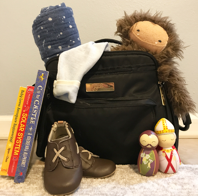 Toys, books, walking shoes, and a blanket all help make traveling with a toddler much easier!