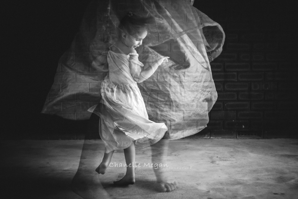 An in camera double exposure image of girl spinning around and edited in Black and white