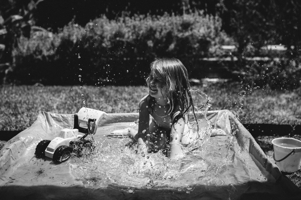 Black and white image of girl splashing in her little pool during a summers day.