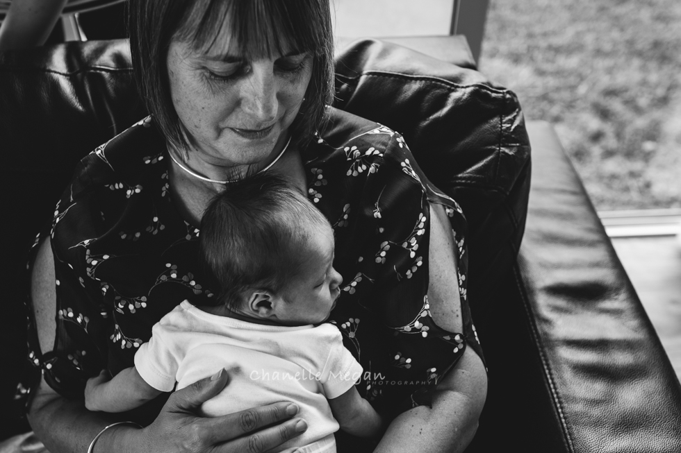 Black and white image of a Grandmother embracing her newest granddaughter.