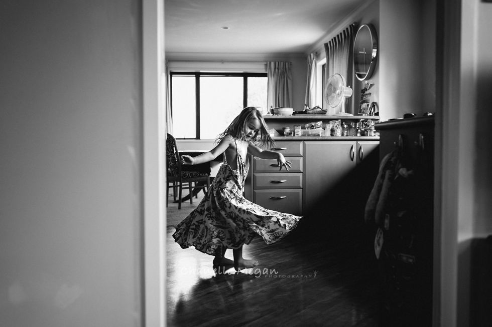 A black and white image of a girl twirling in her kitchen in directional light capturing her movement.