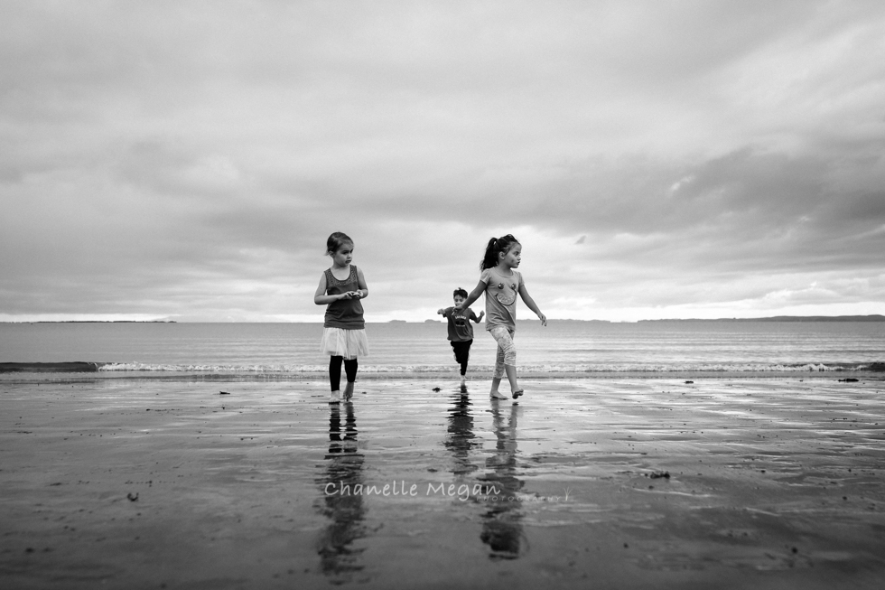 Wide angle shot edited in black and white of three children at the beach walking away from the waters edge.