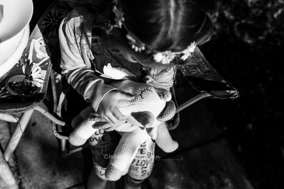 A young girl playing in some harsh light with her unicorn toy edited in black and white.