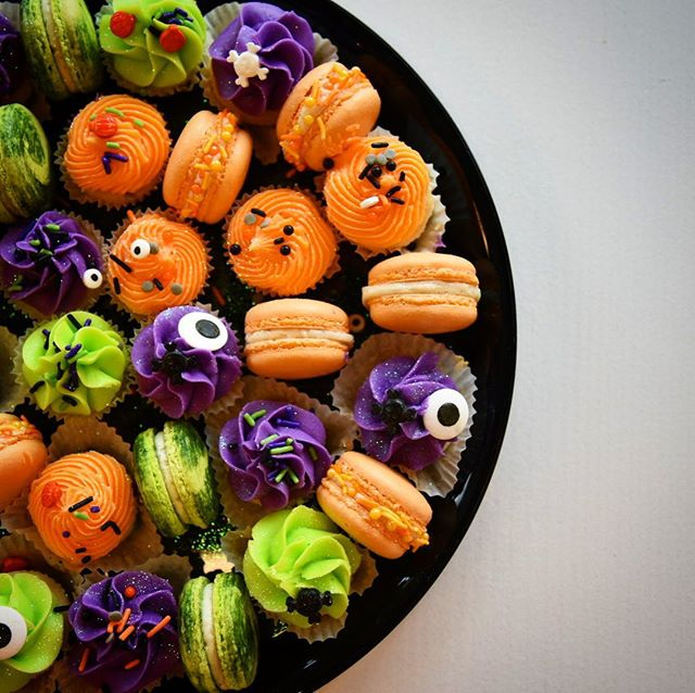 """Our 👻 HALLOWEEN PARTY PLATTER 👻 is now LIVE on the website! . This party platter includes two dozen mini wedding cake cupcakes and a dozen vanilla french macarons, all decorated in spooky, festive Halloween flair! 🎃 . Price is $50.00, all pre-orders are set for a pick up next weekend, and orders are limited, so follow the link in our bio to snatch yours! . Also, because it's science week, we've got a spooky Pumpkin fact for you here too: """"Pumpkin oil has healing properties: a study of second-degree burns in rats found that the oil doubles closing of wounds, which is partly explained by the fact it increases the production of collagen (the main structural protein in connective tissue) by 65%."""" - @forbes Science  Oh, my, gourd, y'all! 😂🤯🎃 #science #halloween"""