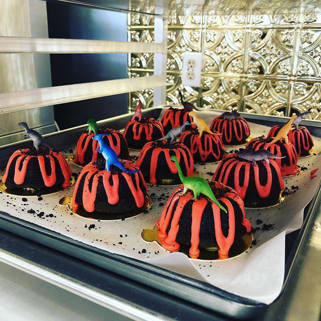 """After baking, filling, covering, drizzling, crumbling, and then topping with take-home dinosaurs, we felt PRETTY PROUD of these Volcano Dino Bundts coming to tomorrow's menu 💪🏻 . Then we remembered our Dino fact for y'all... and it's that a BRAND NEW DINOSAUR was freaking found in August of THIS year 😳🤯 . The team of scientists, led by PhD Student Kimberley Chapelle, recognised that the dinosaur was not only a new species of sauropodomorph, but an entirely new genus. The specimen has now been named Ngwevu intloko which means """"grey skull"""" in the Xhosa language, chosen to honor South Africa's heritage 🇿🇦 . So, we've got volcano Dino bundts tomorrow to celebrate scientific discoveries... and a whole lotta effort 💪🏻 . 📚: @natural_history_museum"""