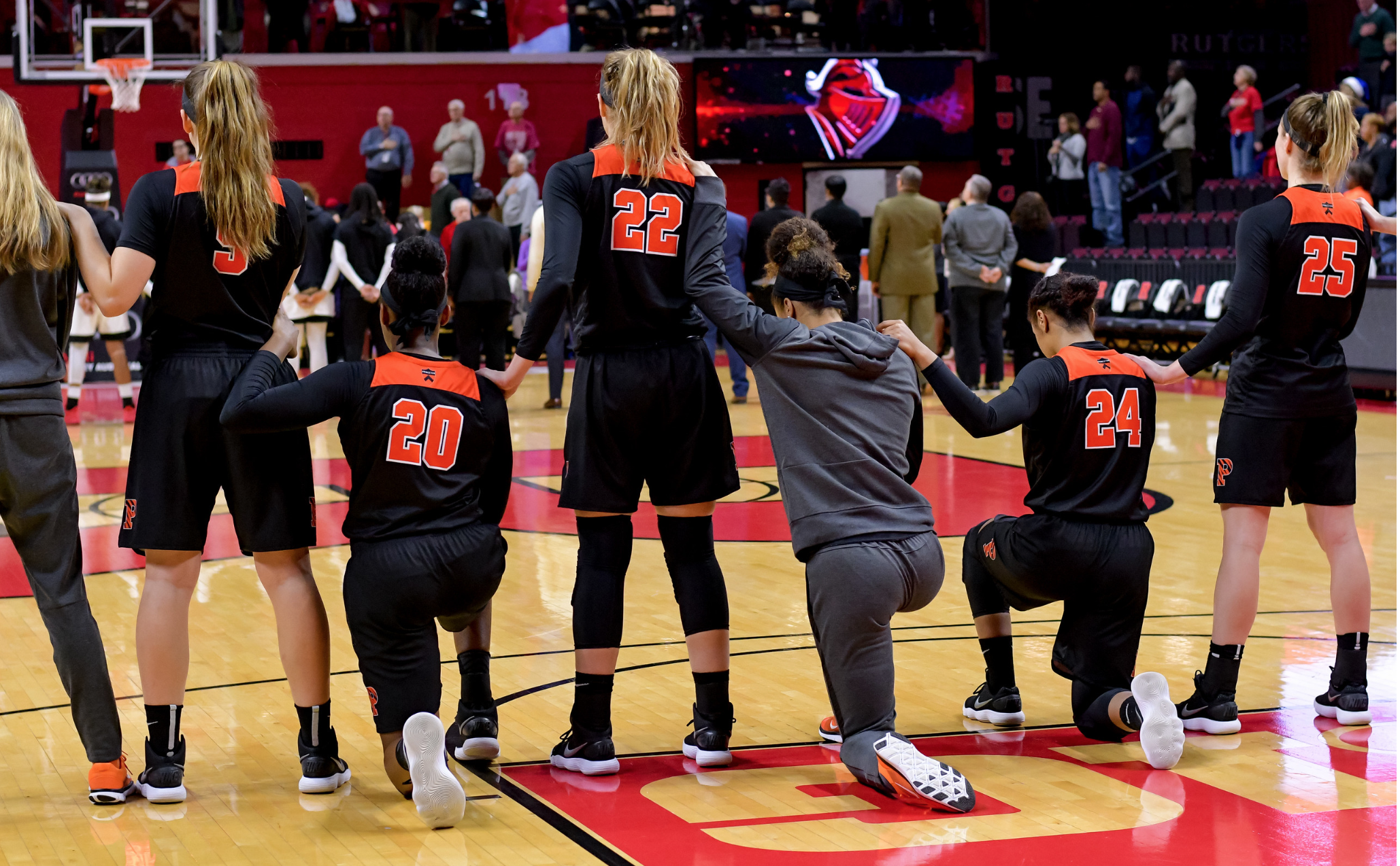 Sydney Jordan (No. 20) takes a knee as well as Qalea Ismail (jumpsuit) and Kenya Holland (No. 24) in a game against Rutgers University.  (Photo by and reprinted with permission from Joel Plummer)