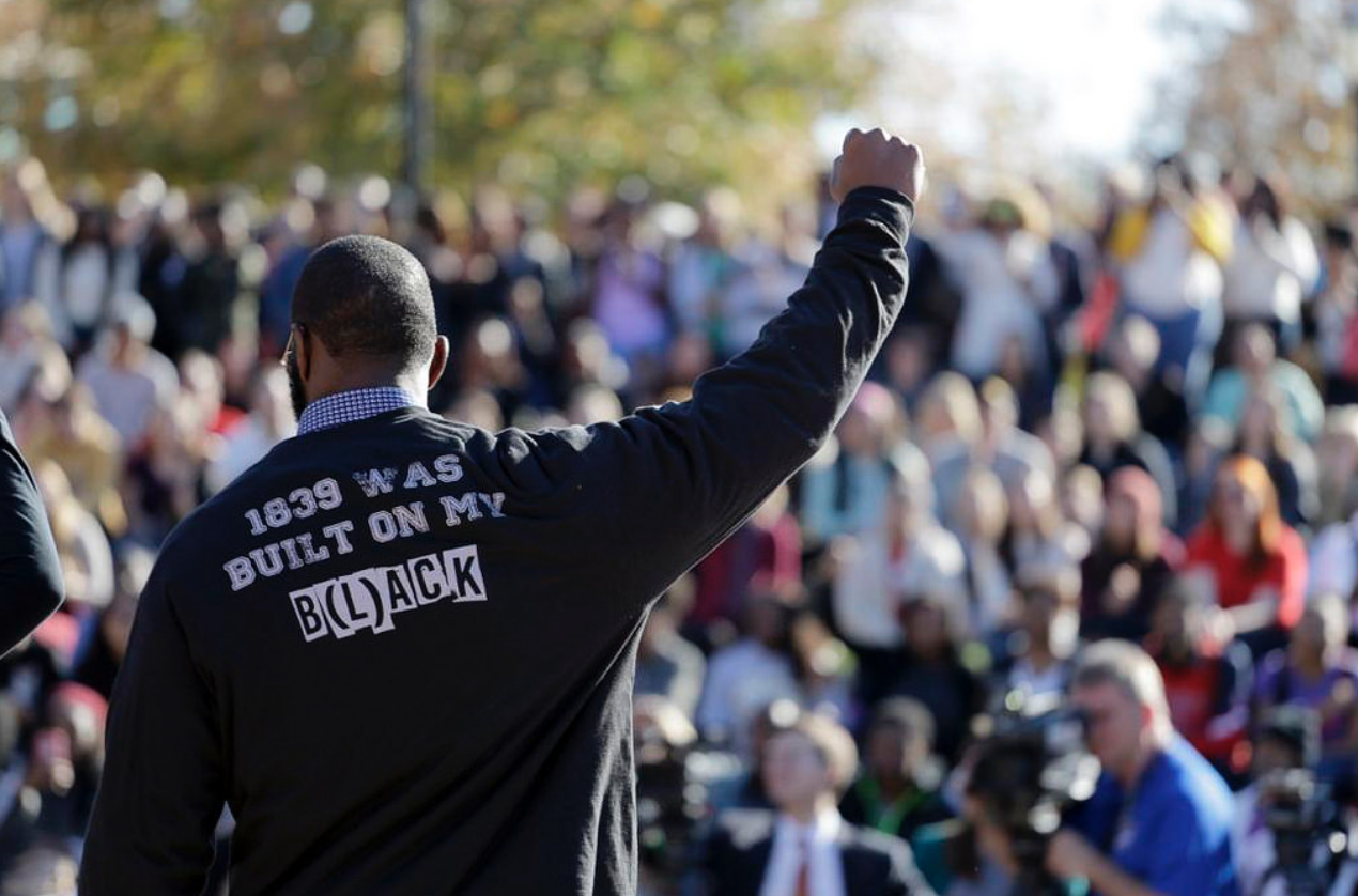 """A member of a student lead protest group called """"concerned student 1950"""" makes a gesture to the crowd that was gathered on campus after the resignation Tim Wolfe.  (Photo by Karen Cyars)"""